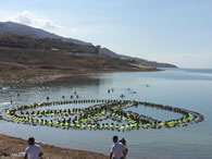 Employees and management from hotels in the Dead Sea area join forces to break the Guinness World Record of the largest floating human image showing a peace sign at the lowest point on earth, at the Dead Sea Spa Hotel Beach, Jordan.